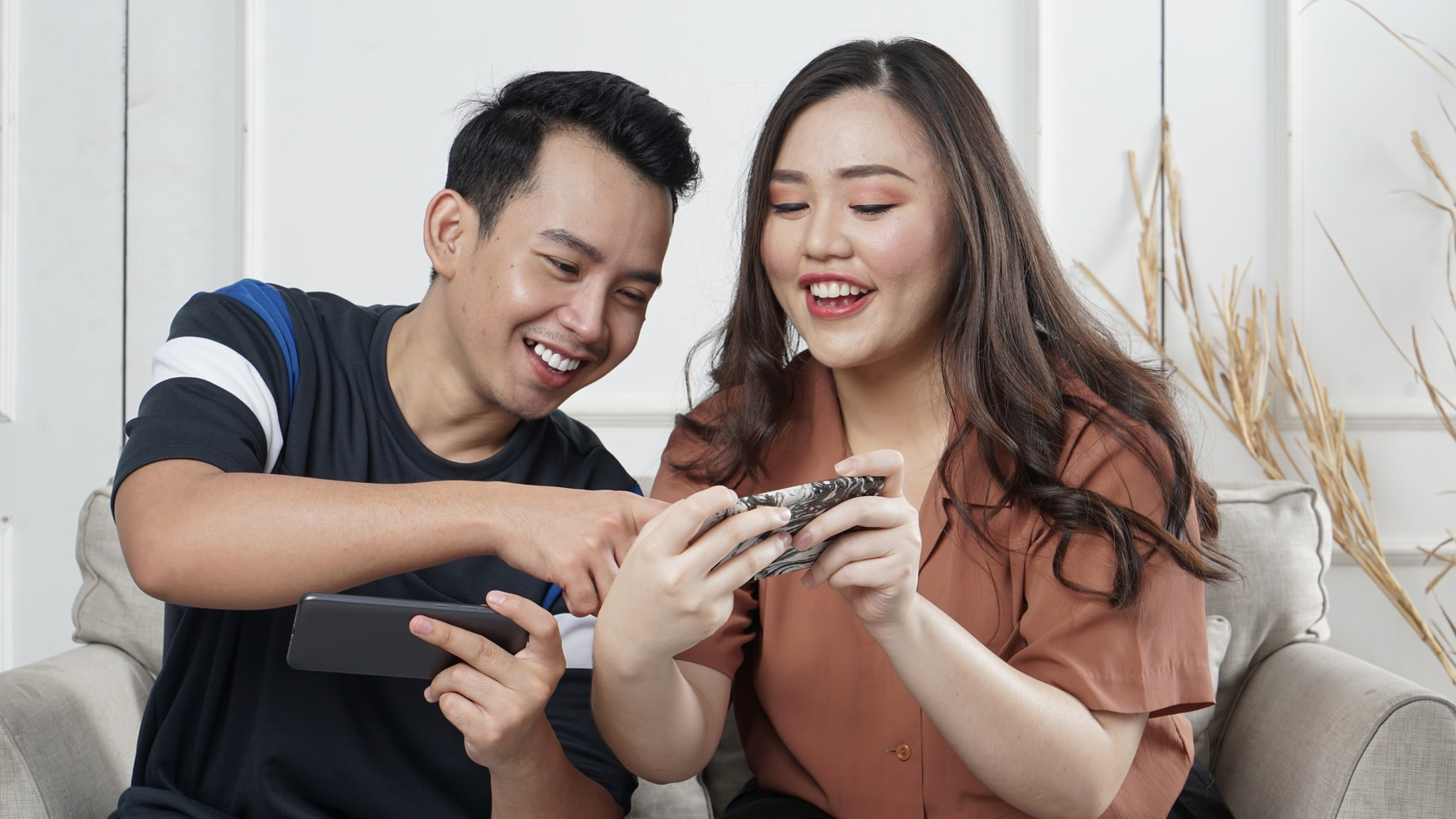 couple smiling at phones